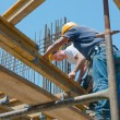 Construction workers placing formwork beams - Stock Photo
