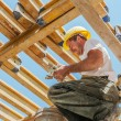 Smiling construction worker busy under slab formwork beams - Stockfoto