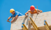 Construction workers nailing cement formwork in place — Stock Photo