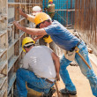Construction builders positioning concrete formwork frames - Stock Photo
