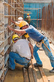 Construction builders positioning concrete formwork frames — 图库照片