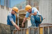 Twee werknemers in de bouw installeren concrete bekisting frames — Stockfoto