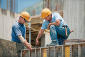 Two construction workers installing concrete formwork frames — Foto de Stock