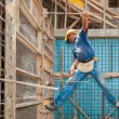 Construction worker balancing between scaffold and formwork fram - Stockfoto