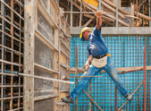 Construction worker balancing between scaffold and formwork fram — Stock Photo