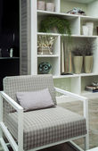 Chair by bookcase — Stockfoto