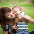Happy little boy in the park with mother — Stock Photo #13291653