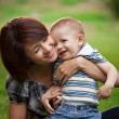 Happy little boy in the park with mother — Stock Photo #13291659