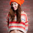 Stock Photo: Beautiful young girl in sweater and cap color