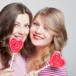 Two girlfriends teens with candy hearts — Stock Photo #18578133