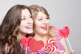 Two girlfriends teens with candy hearts — Stock Photo