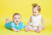 Two kids crawling, isolated on yellow — Stock Photo