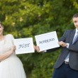 Happy Groom and Bride in park with signs — Stock Photo #31153779
