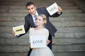 Happy Groom and Bride in a park with signs — Stock Photo