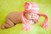 Beautiful sleeping baby wearing a striped hat — Stock Photo
