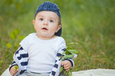 Baby boy sitting on the grass — Stockfoto