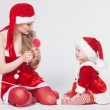 Happy mother with little daughter iin the Santa Claus clothes — Stok fotoğraf