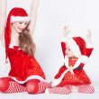 Happy mother with little daughter iin the Santa Claus clothes — Stock fotografie