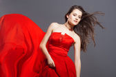 Sexy woman in fluttering red dress — Stockfoto