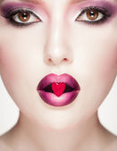Glamour red lips with ice heart — Stock Photo