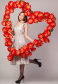 Beautiful woman with heart of flowers — Stock Photo