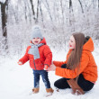 Mother and daughter having fun in the winter forestv — Stock Photo
