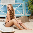 Sexy young woman in bikini standing in beach bungalow — Stock Photo