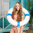 Sexy young woman in bikini standing in beach bungalow with Lifebuoy — Stock Photo