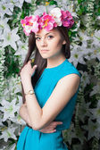 Beautiful and fashion young woman near the wall of flowers — Foto de Stock