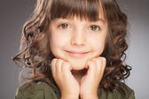 Happy little girl a on grey background — Stock Photo