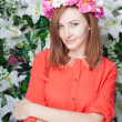 Beautiful and fashion young woman near the wall of flowers — Stock Photo #46733413