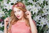 Hermosa y moda joven cerca de la pared de flores — Foto de Stock