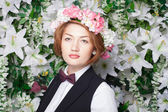 Beautiful and fashion young woman near the wall of flowers — Stock Photo