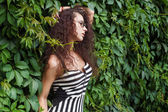Fashion and beautiful young woman in a green wall of leaves — ストック写真