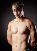 Muscular young sexy nude man on studio — Stock Photo