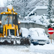 Yellow Bulldozer Snow Plowing Street In Urban Area - Stock Photo
