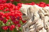 A Stone Lion Statue in a Yard Setting With Flowers — Stock Photo