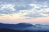 Early morning in the mountains. Clouds and fog at sunrise. — Stock Photo