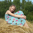 Stock Photo: GIRL LAYING ON STRAW BAIL