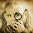 Royalty-Free Stock Photo: Girl looking through magnifier. Vintage styled shot