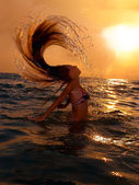 Girl in the sea at sunset with splash — Stock Photo