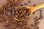Spoon with coffee beans on wooden background — Stock Photo