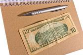 Ten dollars on notebook — Stock Photo