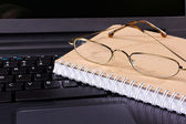 Glasses and notebook lie on the keyboard — Zdjęcie stockowe