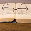 Glasses lying on retro book — Stock Photo
