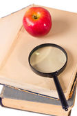 Age-old books, apple and magnifying glass — Stock Photo