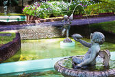 Cherubs water fountain in tropical garden — Stock Photo
