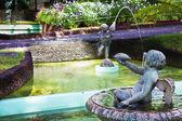 Cherubs water fountain in tropical garden — Stock Photo