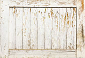 Wooden wall with white paint is severely weathered and peeling  — Stock Photo