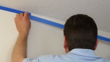 Man Applying Blue Painter's Tape on Wall Below Ceiling — Stock Video